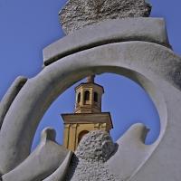 """Suggestiva immagine della Torre Civica vista attraverso la scultura """"Volo negato"""""""